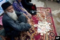 FILE - Pakistan's humanitarian leader Abdul Sattar Edhi collects donations at a roadside in Peshawar, Pakistan, Aug. 2, 2010.