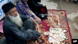 FILE - Pakistan's humanitarian leader Abdul Sattar Edhi collects donations at a roadside spot in Peshawar, Pakistan, Aug. 2, 2010.
