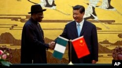 Presiden China Xi Jinping (kanan) berjabat tangan dengan Presiden Nigeria, Goodluck Jonathan di Beijing hari Rabu (10/7).