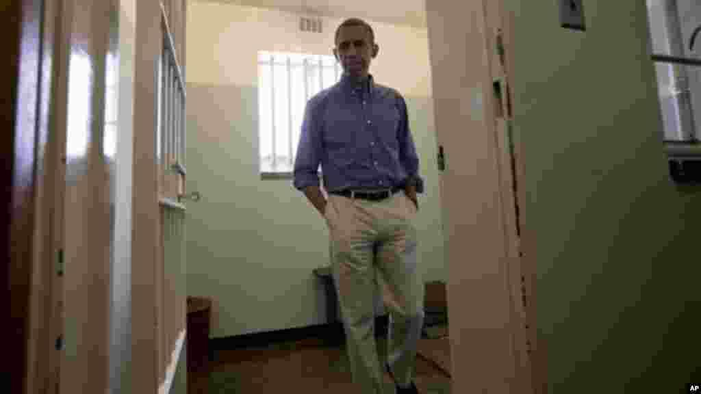 President Obama walks from Mandela's prison cell No. 5, on Robben Island.