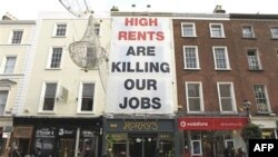 Biểu ngữ treo trước khu cửa hàng than phiền tiền thuê cơ sở cao dẫn đến tình trạng mất công ăn việc làm