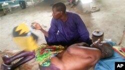 Un homme essaie de calmer la douleur d'un blessé à Baga, le 21 avril 2013