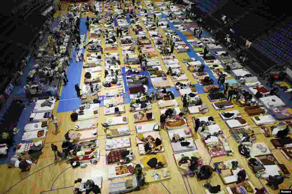 Evacuees from the Serbian town of Obrenovac are seen lying on beds in a shelter hall in Belgrade.