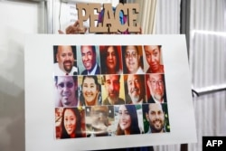 FILE - A poster showing all 14 victims is displayed during an interfaith memorial service at the Islamic Center of Redlands for the victims of the San Bernardino mass shooting, Dec. 6, 2015 in Loma Linda, California.