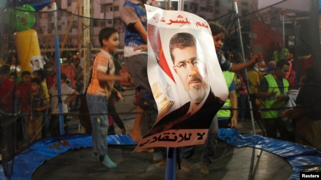 Children of supporters of deposed Egyptian president Mohamed Morsi jump on a trampoline in a makeshift funfair in Cairo's Rabaa al-Adawiya Square, August 11, 2013.