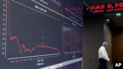 A man walks behind screens showing a graph of stocks at the Athens Stock Exchange, in Athens, October 24, 2011.