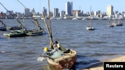 FILE - A fisherman cleans his boat beneath Maputo's skyline in Mozambique on Aug. 15, 2015. A member of the Renamo party was killed Oct. 8, 2016, on a Maputo beach.