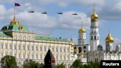 Russian military helicopters fly in formation with the Kremlin and the Ivan the Great Bell Tower seen in the foreground, in central Moscow May 3, 2014.