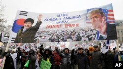 A banner showing pictures of impeached South Korean President Park Geun-hye and U.S. President Donald Trump is displayed as supporters of Park wave flags of the United States and South Korea during a rally opposing her impeachment in Seoul, South Korea,