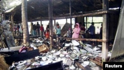 People look at burnt textbooks after a primary school which was supposed to be used as a polling booth was set on fire, in Feni, Bangladesh, Jan. 4, 2014.