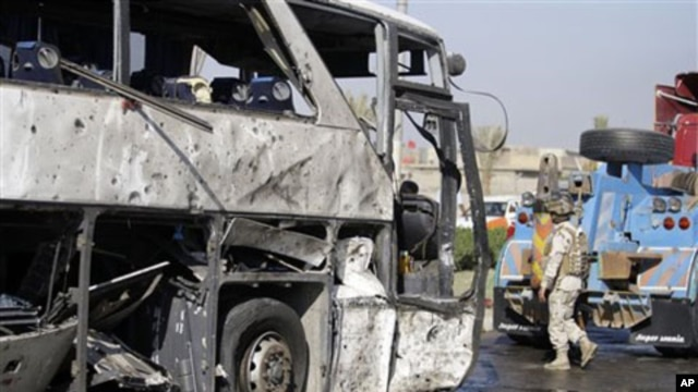 An Iraqi army soldier inspects a destroyed bus in Baghdad, 04 Dec 2010