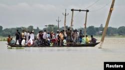 4일 인도 북동부 아삼주 아시가르 마을에서 폭우로 홍수가 발생하자 주민들이 뗏목을 타고 대피하고 있다.