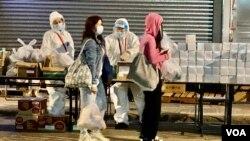 1月26日晚油麻地封鎖區內需要接受突襲式強制檢測的居民,領取政府派發的食物等物資。(美國之音 湯惠芸拍攝)