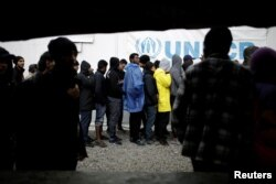 Refugees and migrants line up to receive their lunch provided by the Greek authorities, at a makeshift camp next to the Moria camp on the island of Lesbos, Greece, Nov. 30, 2017.