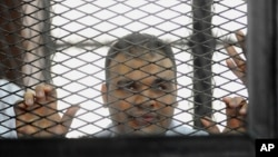 FILE - In this Wednesday, Dec. 4, 2013 file photo, Mohammed Badr, a cameraman for Al-Jazeera Mubasher Misr, appears at a court in Cairo, Egypt.