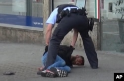 In this grab taken from video, police arrest a man in Reutilingen, Germany, July 24, 2016. A Syrian man killed a woman with a machete and wounded two others outside a bus station in the southwestern city before being arrested.