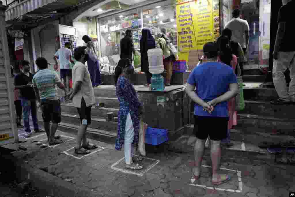 با گرفتن فاصله از هم دیگر به دلیل شیوع ویروس کرونا مردم برای خرید مایحتاج غذایی در بمبئی، هندوستان به صف ایستادهاند.