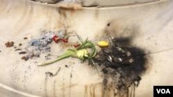 Sisa-sisa barang yang terbakar di tempat penghormatan di Washington untuk remaja Muslim Nabra Hassanen terbunuh, 21 Juni 2017. (E. Sarai / VOA)