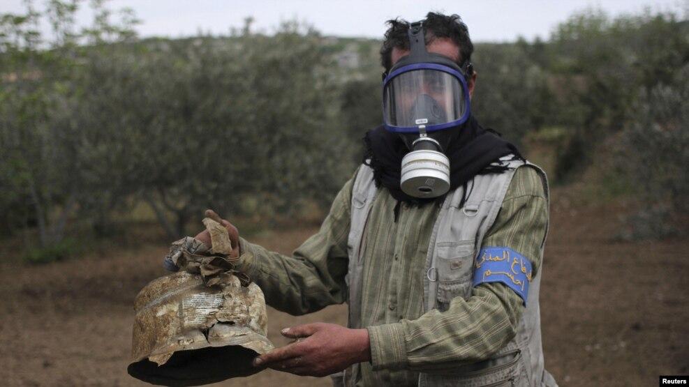 Một thành viên của lực lượng Phòng vệ Dân sự cầm trên tay một vỏ hộp được cho là chứa khí gas clorine, Syria, ngày 03 tháng 05 năm 2015.