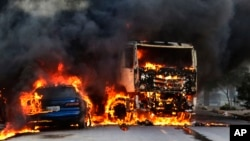 Vehicles burn in the street after attacks in the city of Fortaleza, northeastern Brazil, Jan. 3, 2019.