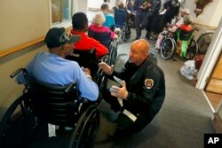 Metrju Mejer iz tima za spasavanje i potragu iz Nebraske, desno, ragovara sa ratnim veteranom iz Korejskog rata Romanom Vigsom, 87, dok ga evakuišu u prihvatilište u crkvi, kao predostrožnost zbog mogućog potapanja grada.