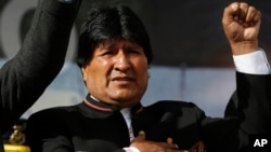 One day after a referendum on expanding presidential term limits, Bolivia's President Evo Morales sings his national anthem at a signing ceremony for the expansion of a road that connects the capital with the nearby city of El Alto, in La Paz, Bolivia, Mo