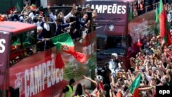 Les joueurs de l'équipe nationale portugaise montés sur un bus à toit ouvert, sont accueillis par une foule des supporters en liesse dans les rues de Lisbonne, Portugal, 11 juillet 2016. epa/ SETVEN GOVERNO