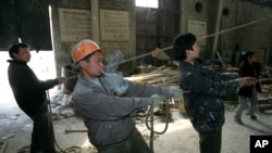 A migrant worker from Xi'an labors in a sculpture manufacturing company in one of Beijing's industrial neighborhoods Wednesday, March 30, 2005. Beijing announced the end of its rules limiting the life and work of immigrants Friday. While praising the loca
