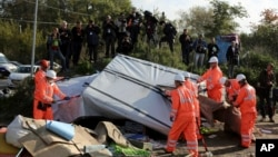"Crews start to demolish shelters in the makeshift migrant camp known as ""the jungle"" near Calais, northern France, Oct. 25, 2016."