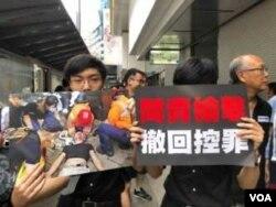 學生手持6.12 警民眾流血大衝突,被警方擊傷的示威者照片及遊行標語(美國之音湯惠芸攝)