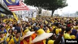 """Para demonstran mendengarkan pidato dalam protes yang diorganisir oleh kelompok pro-demokrasi """"Bersih"""" di Kuala Lumpur (29/8). (Reuters/Olivia Harris)"""