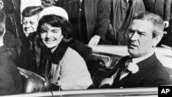 Presiden John F. Kennedy dan istrinya, Jacqueline mengendarai limusin bersama Gubernur Texas, John Connally, dari Bandara Udara Love Field di Dallas, Texas, sesaat sebelum penembakan, 22 November 1963. (AP Photo)