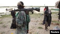 Des habitants de Turkana porte une mitraillette sur l'épaule sur la berge au lac Turkana, près deTodonyang au nord Kenya, le 25 novembre 2014.