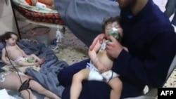 Доброволец оказывает помощь детям в больнице после предполагаемой химической атаки на удерживаемый боевиками город в Сирии. Photo: Syrian Civil Defense White Helmets (AFP ). Photo taken from Poligraph.info website. 8 апреля 2018 г.
