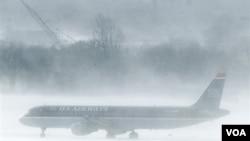 En el aeropuerto de Filadelfia un avión de U.S. Airways aguarda en medio de la nevisca. Muchos pasajeros debieron esperar dentro de los aviones.