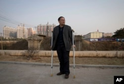 FILE - Zhou Wangyan, head of the Liling city land resources bureau, stands with crutches near a plot of land under development in Liling city in central China's Hunan province.
