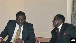 Zimbabwean President Robert Mugabe, right, chats to Prime Minister Morgan Tsavangirai during their end of year press conference at State House in Harare, saying they were dispelling rumors of disunity in the Government of National Unity, Dec. 20, 2010