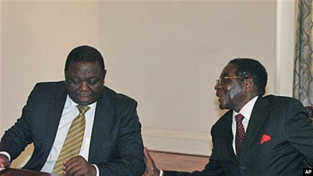 Zimbabwean President Robert Mugabe, right, chats to Prime Minister Morgan Tsavangirai during their end of year press conference at State House in Harare, saying they were dispelling rumors of disunity in the Government of National Unity, December 20, 2010