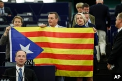 Belgium members of the European Parliament, Anneleen Van Bossuyt, left, Mark Demesmaeker and Helga Stevens, right, display a Catalan flag in support of the disputed independence vote Sunday in Catalonia during a session at the European Parliament.