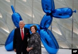 """Eli Broad and his wife Edythe pose for a photo in front of a Jeff Koons sculpture at Broad's new museum called """"The Broad"""" in downtown Los Angeles, Sept. 16, 2015."""