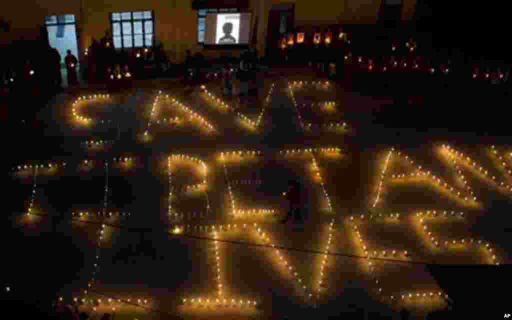 Exile Tibetans arrange candles to read 'Save Tibetans Lives' during a protest vigil to remember Tibetans who have self-immolated in Tibet this year, in Dharmsala, India, Saturday, Oct. 8, 2011.