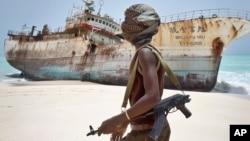 En esta foto tomada el domingo, 23 de septiembre de 2012, el pirata somalí enmascarado Abdi Ali pasa por delante de un buque pesquero taiwanés que encallo en la costa después de que los piratas recibieran un rescate y liberó a la tripulación.