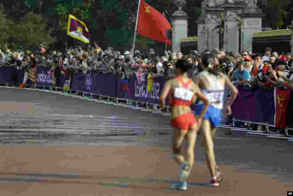 A Tibetan flag, left, and a China's flag are hold by spectators during the women's 20-kilometer race walk, at the 2012 Summer Olympics, Saturday, Aug. 11, 2012, in London.