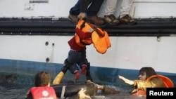 지난해 10월 터키에서 에게 해를 건너 시리아에 도착한 난민들이 자원봉사자들의 도움으로 구조되고 있다. 어린아이 한 명이 구조선으로 올려지고 있다. (자료사진)