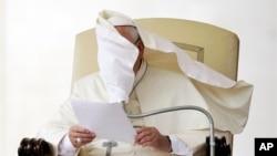 Le visage du pape François couvert par un pan de sa soutane soufflé par le vent pendant qu'il lit un discours durant une audience générale à la place St Pierre, au Vatican, mercredi 15 octobre, 2014.