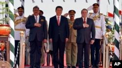 巴基斯坦新闻部发布的照片显示,中国主席习近平和巴基斯坦总统侯赛因(左)总理谢里夫(右)在伊斯兰堡的空军基地检阅仪仗队(2015年4月20日)