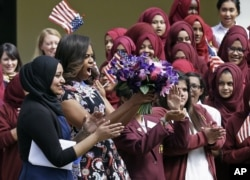U.S. first lady Michelle Obama is greeted by pupils and teachers at Mulberry School for Girls in east London, June 16, 2015.