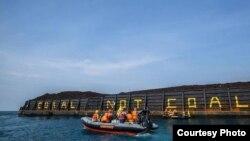 Aktivis Greenpeace menulis Coral not Coal di lambung tongkang batubara di Karimunjawa, sebagai ilustrasi. (Foto: Greenpeace Indonesia)
