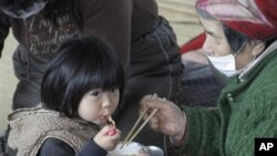 A child eats noodle during a lunch at an evacuation center in Ofunato, Iwate Prefecture, Japan, Sunday, March 20, 2011, after the March 11 earthquake and tsunami devastated the area. (AP Photo/Koji Sasahara)
