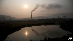 Smoke rises from a brick kiln on the outskirts of Gauhati, India, Monday, Jan. 26, 2015. The World Meteorological Organization reports greenhouse gas concentrations in the atmosphere last year hit a new high and 2015 looks as though it will be another record-breaking year for gases that cause global warming.